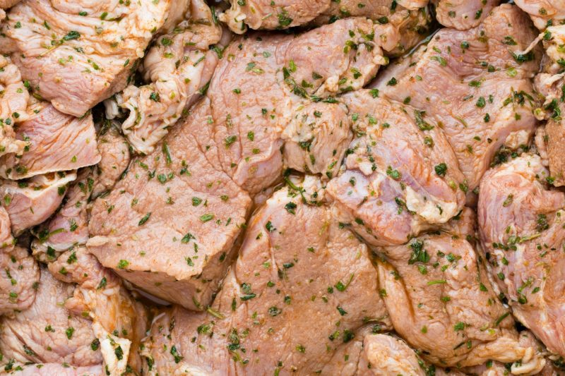 Fresh pork meat pieces in marinade.